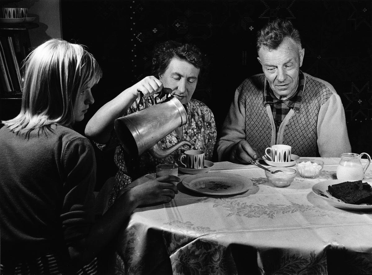 1961, Ásmundur Sveinsson og Ingrid Sveinsson við dúkað kaffiborð á heimili sínu. Ingrid hellir í bollana. Ljósmynd: © Hermann Schlencker